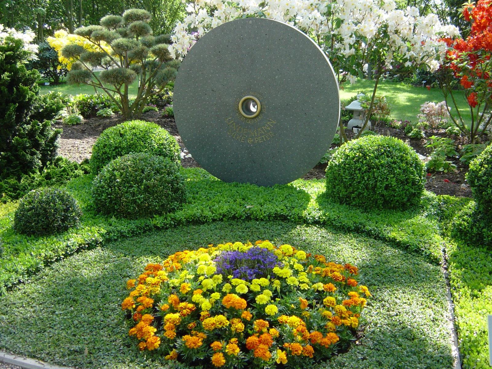 Ein außergewöhnlicher Grabstein mit einer schönen Bepflanzung zieht die Blicke der Besucher auf sich.