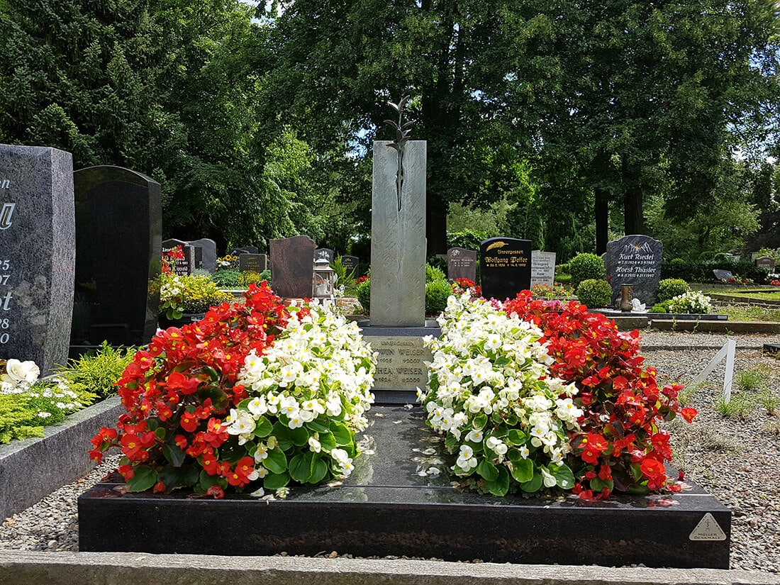 Im Sommer steht die Natur in voller Blüte. Die Grabumrandung sorgt für eine saubere Abgrenzung der Grabfläche vom Weg.