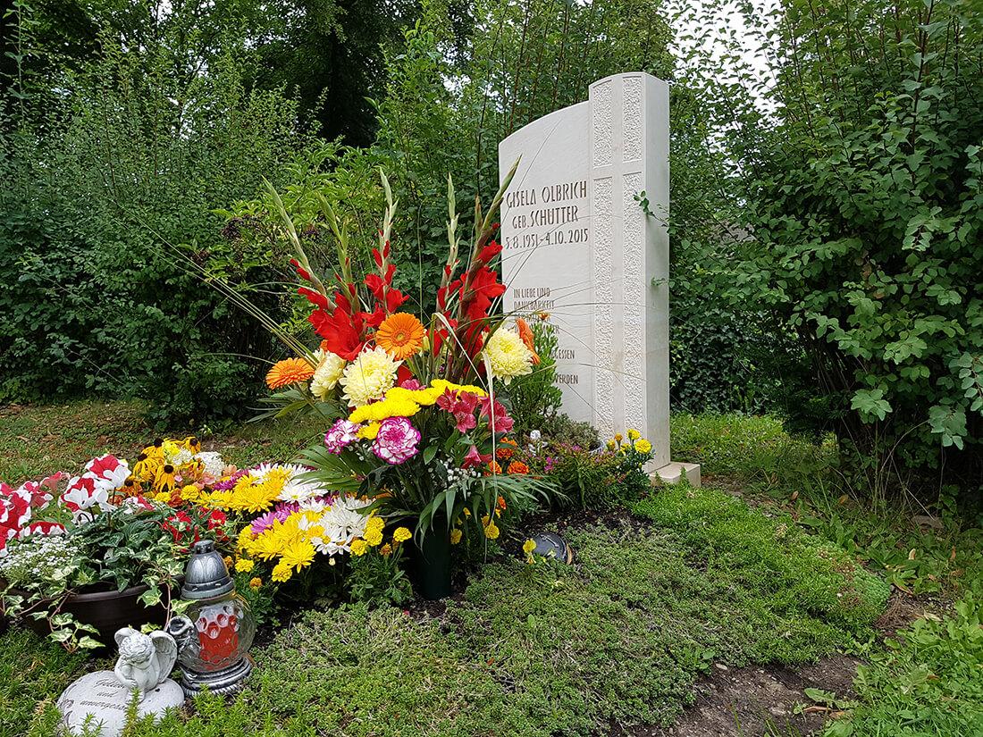Eine üppige Grabbepflanzung hebt das Grab auf dem Friedhof hervor.