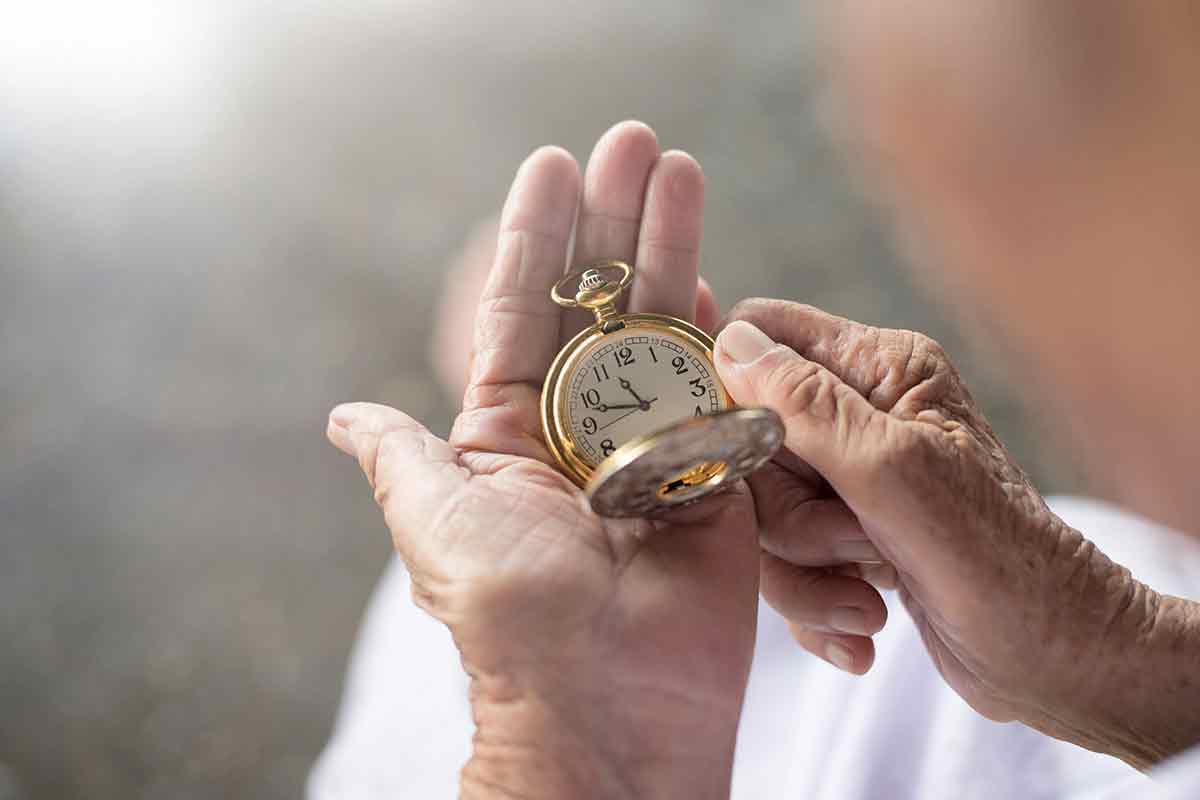 Alter Mensch blickt auf Taschenuhr