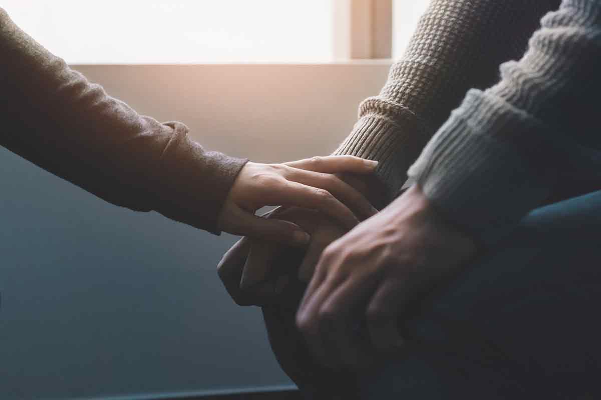 Hände zweier Menschen spenden sich Trost