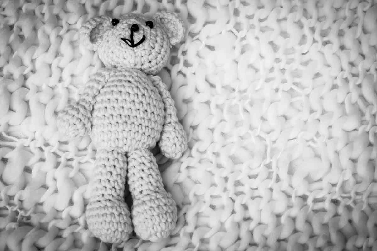 Teddybär liegt auf Decke traurig