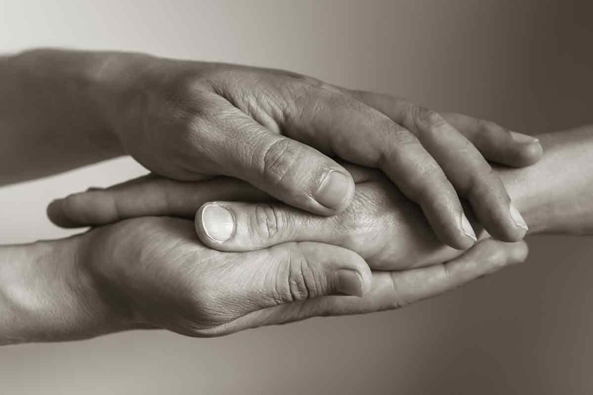 Hände liegen aufeinander zum Trost spenden