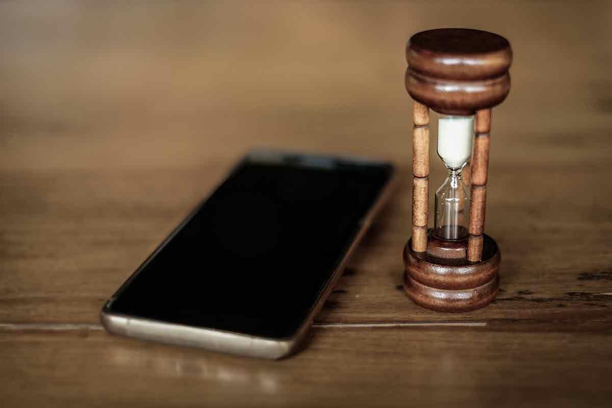 Handy auf Tisch neben Sanduhr