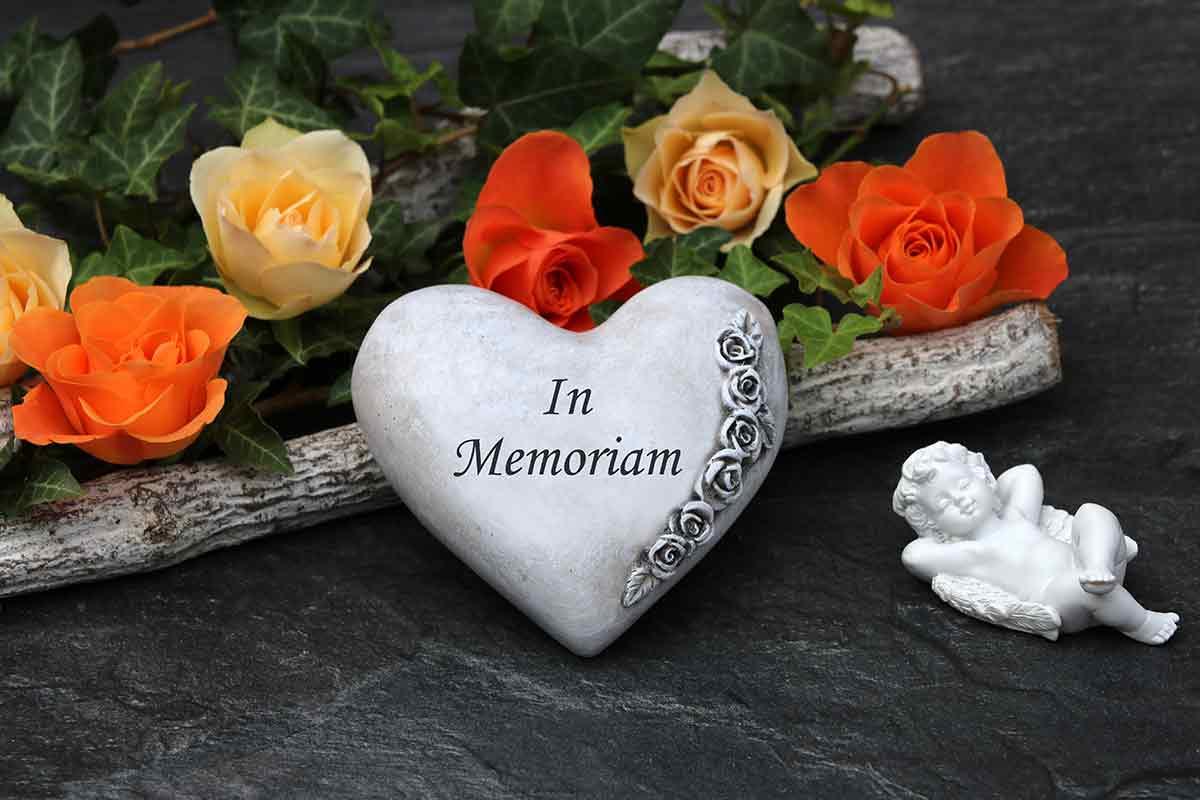 Grabschmuck in Herzform mit Trauerspruch neben Rosen