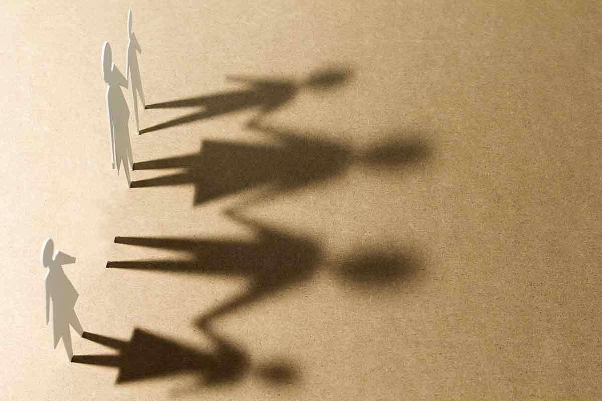 Familie aus Papierfiguren mit Schatten