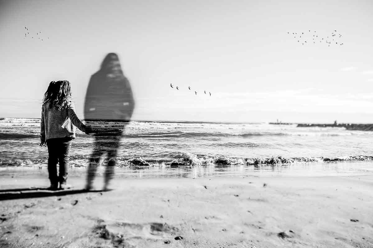 Kind steht mit Umriss verstorbener Mutter am Strand.