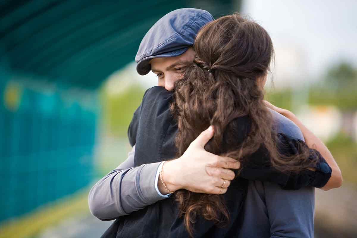 Frau umarmt Mann zu traurigem Anlass