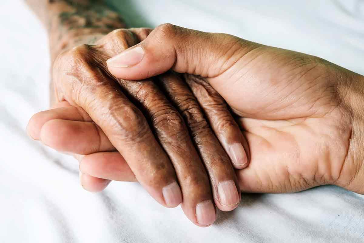 Junge Hand hält alte auf Krankenhausbett