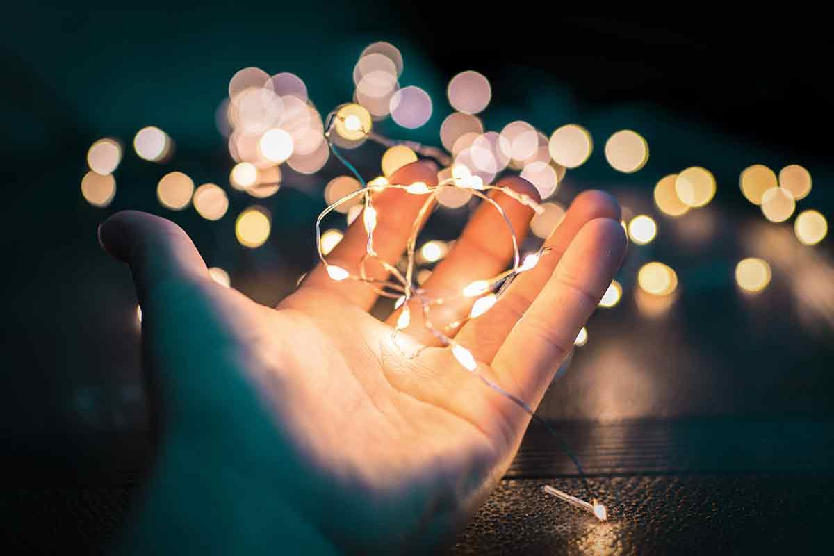 Hand hält Lichterkette im Dunkeln.