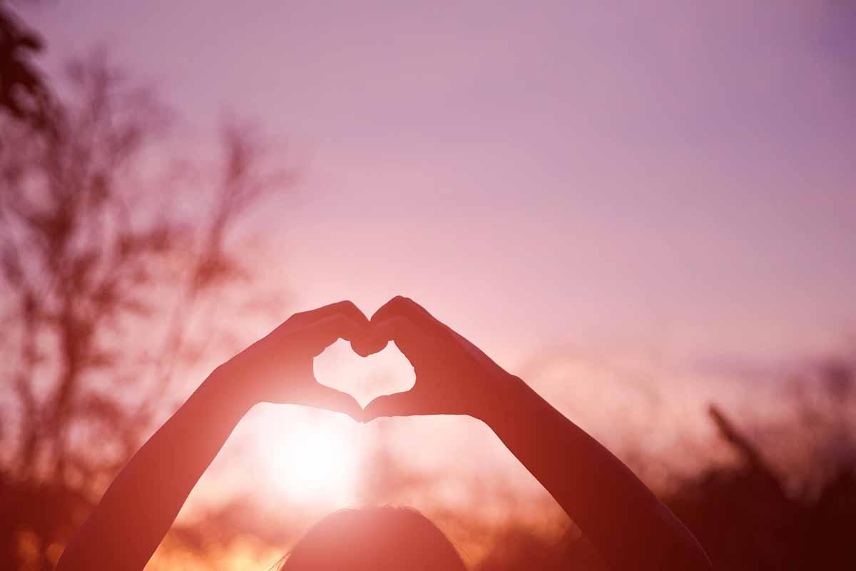 Hände formen Herz im Himmel bei Sonnenuntergang
