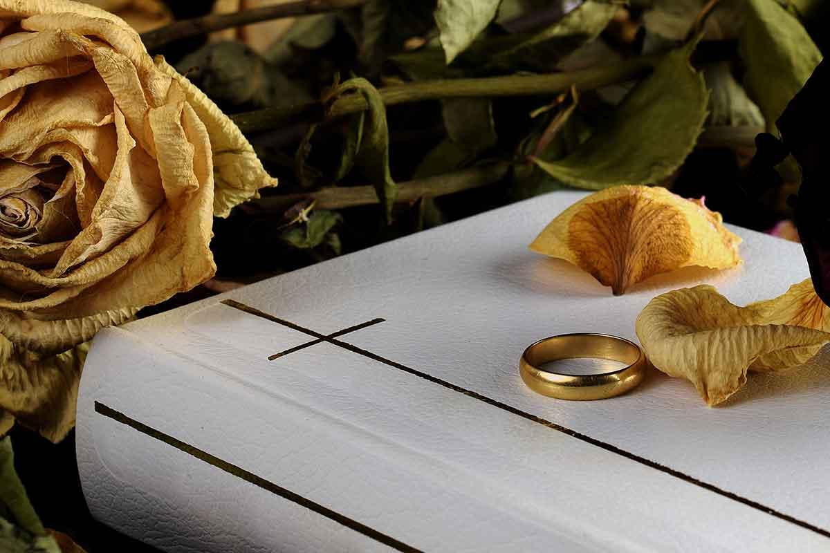 Bibel mit Ehering und vertrockneten Blumen