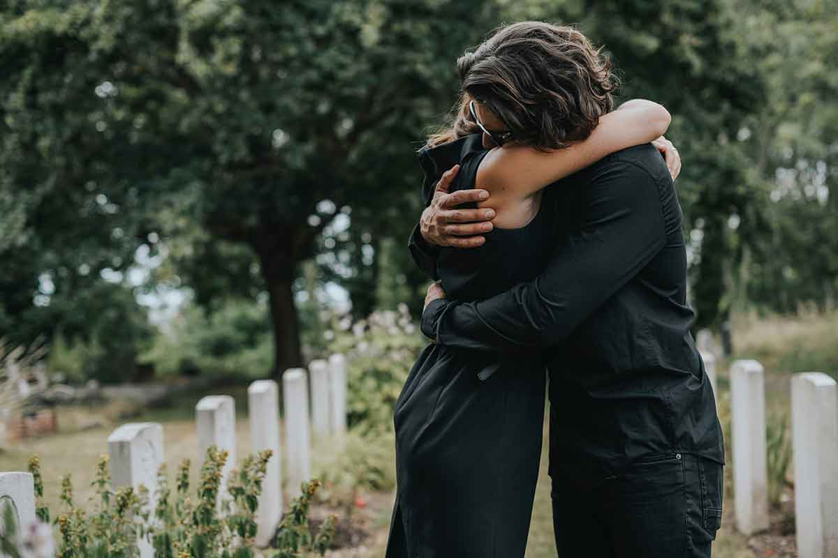 Frau und Mann umarmen sich auf Friedhof