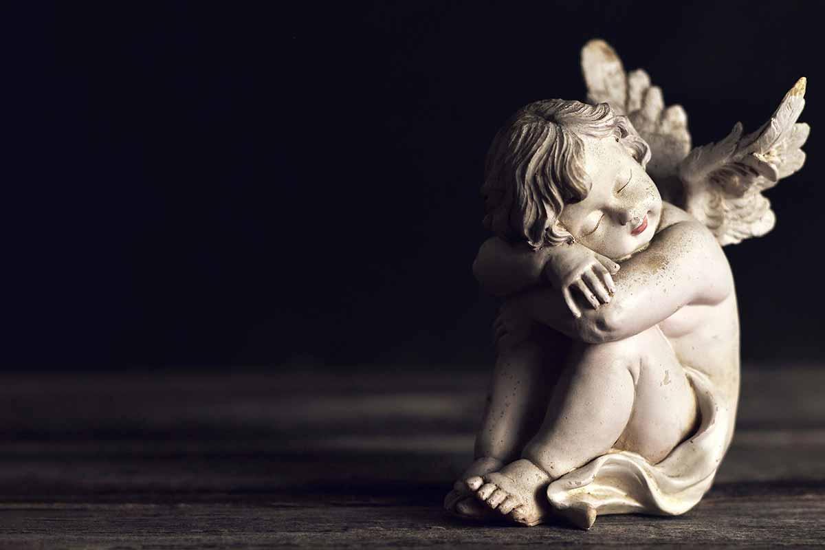 Engel-Figur auf Holz vor dunklem Hintergrund