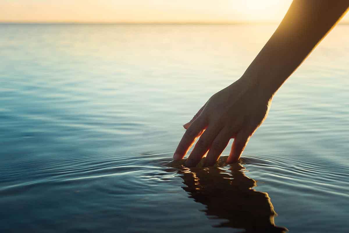 Hand in ruhigem Meer Sonnenuntergang