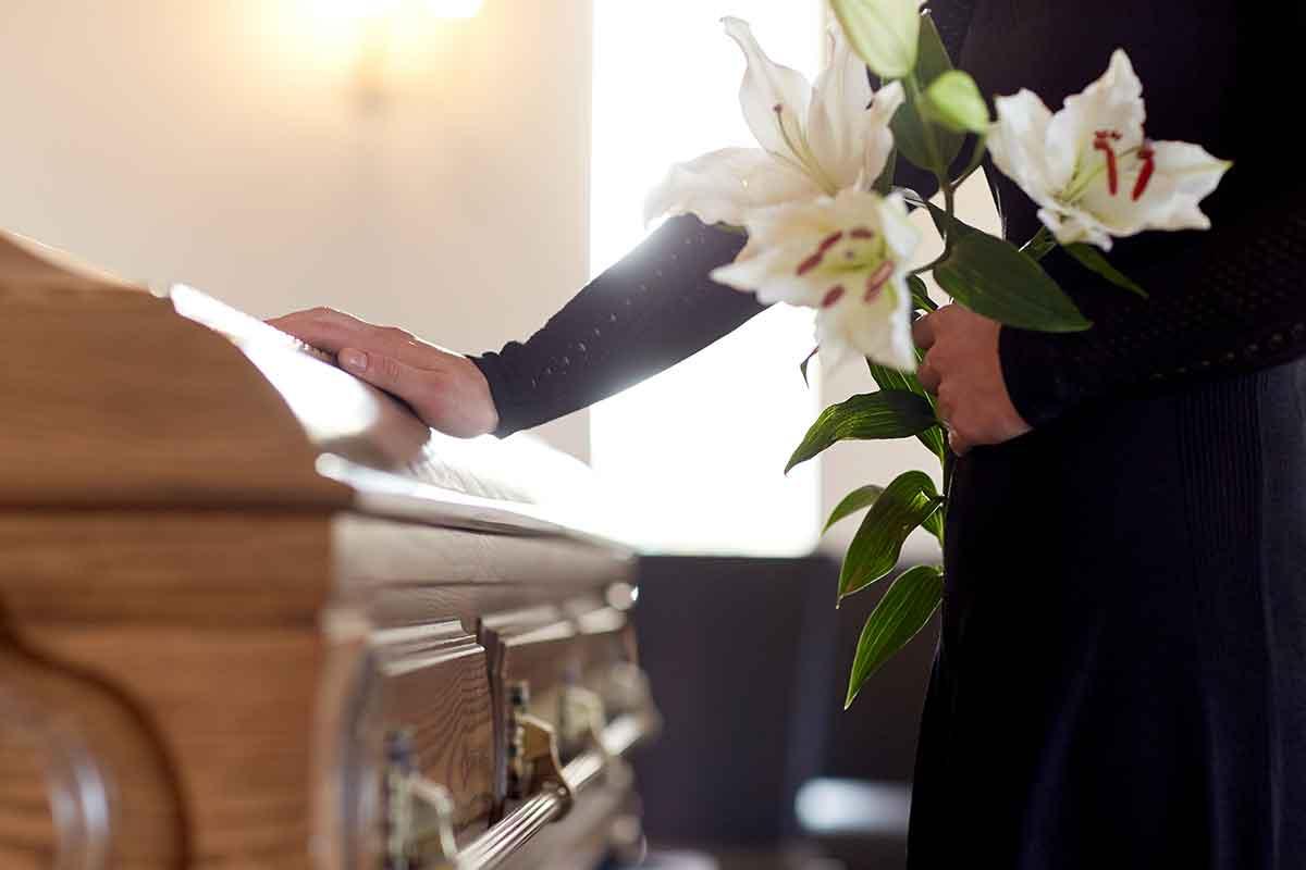 Frau mit Blumen neben Sarg auf Beerdigung